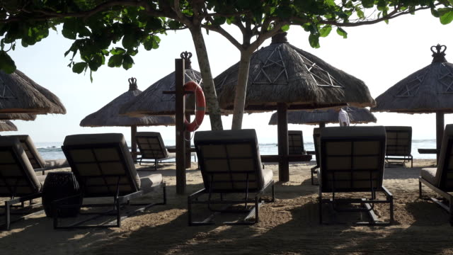 Sandy-beach-of-the-tropical-resort-with-umbrellas-and-chaise-lounges