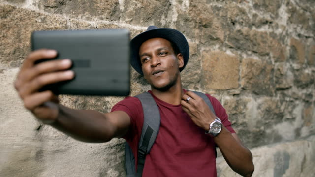Happy-african-american-tourist-man-having-online-video-chat-using-tablet-computer-while-travelling-in-Europe