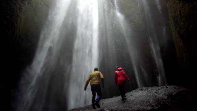 Junge-Brautpaar-stehend-unter-wunderschönen-Wasserfall-Gljufrabui-in-Island-und-hebt-die-Hände-Gefühl-von-Freiheit-und-Freude