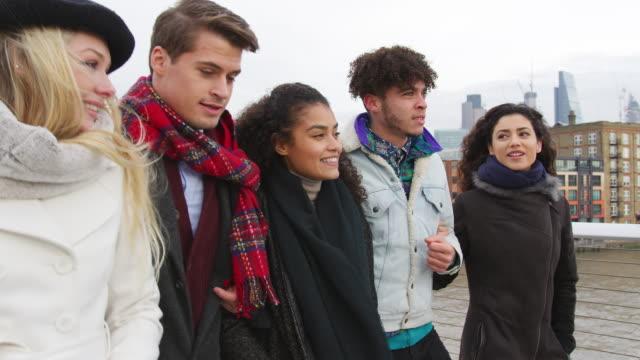 Gruppe-junger-Freunde-zu-Fuß-über-Millennium-Bridge-In-London