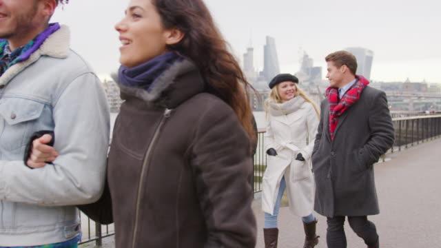 Freunde-zu-Fuß-entlang-Südufer-bei-Winter-Besuch-in-London