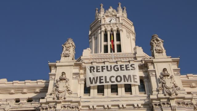 Bandera-de-refugiados-Bienvenido-a-la-fachada-de-Palacio-de-comunicaciones-con-Madrid