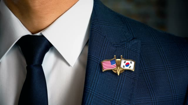 Businessman-Walking-Towards-Camera-With-Friend-Country-Flags-Pin-United-States-of-America---South-Korea