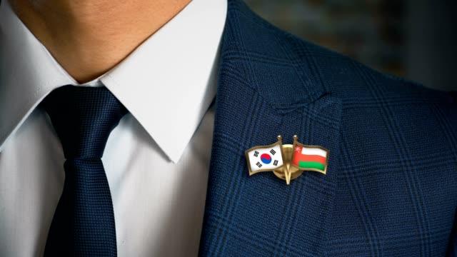 Empresario-caminando-hacia-cámara-con-amigo-país-banderas-Pin-Corea-del-sur---Omán