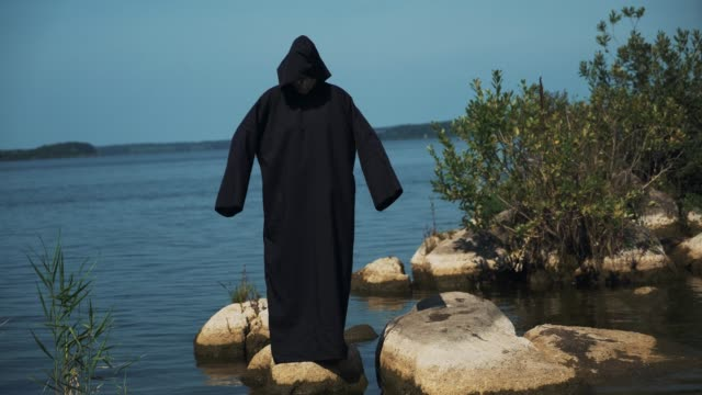 Woman-devil-in-black-cape-and-hood-on-stones-near-the-river-