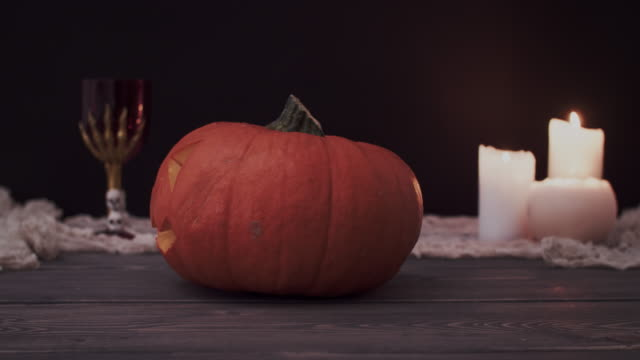 Halloween-pumpkin-with-scary-face-and-burning-candles