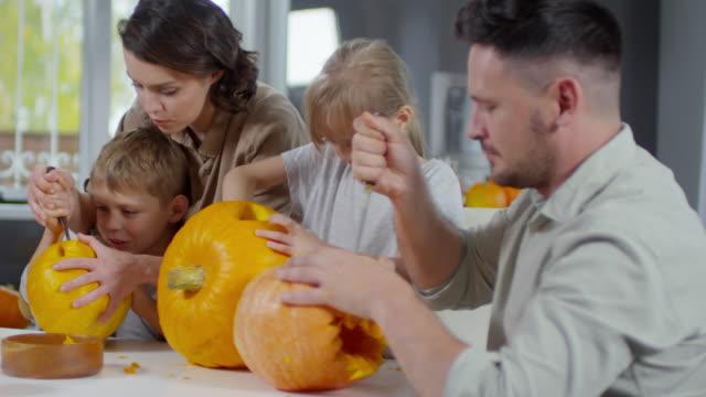 Mann-lächelnd-in-die-Kamera-während-der-Herstellung-Halloween-Kürbisse-zusammen