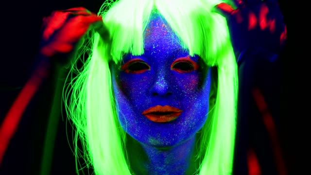 Woman-with-UV-face-paint-wig-glowing-clothing-dancing-in-front-of-camera-face-close-up-of-make-up-Caucasian-woman-