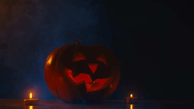CINEMAGRAPH---CU-Halloween-carved-pumpkin-Jack-o-Lantern-with-candles-fog-in-the-background