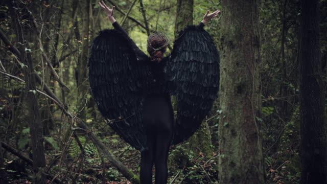 4k-Halloween-mujer-oscura-del-ángel-con-alas-de-negro-en-el-bosque-de-manos-se-levantan