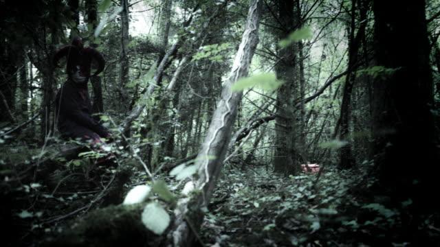 4k-Halloween-Shot-of-a-Child-in-Joker-Costume-Hiding-in-Woods