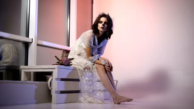 Hermosa-chica-de-pelo-oscuro-con-la-imagen-de-la-novia-muerta-en-vestido-blanco-y-velo-de-participar-en-la-fiesta-de-halloween-Mujer-joven-en-traje-está-sentado-en-la-sala-Espíritu-creativo-maquillaje-espeluznante-miedo