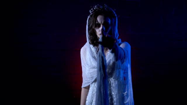 Fantasma-de-la-novia-muerta-sola-en-vestido-de-novia-blanco-y-velo-con-cara-triste-moviendo-su-mano-Maquillaje-contra-fondo-de-terror-en-chica-Scary-halloween-apperance-Misteriosa-mujer