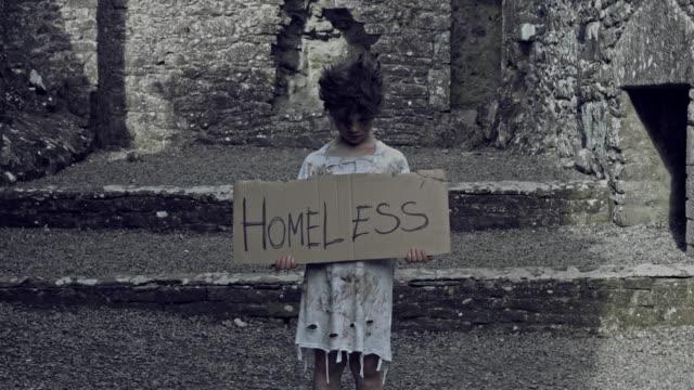 """4k-Horror-Shot-of-an-Abandoned-Child-Holding-""""Homeless""""-on-cardboard"""