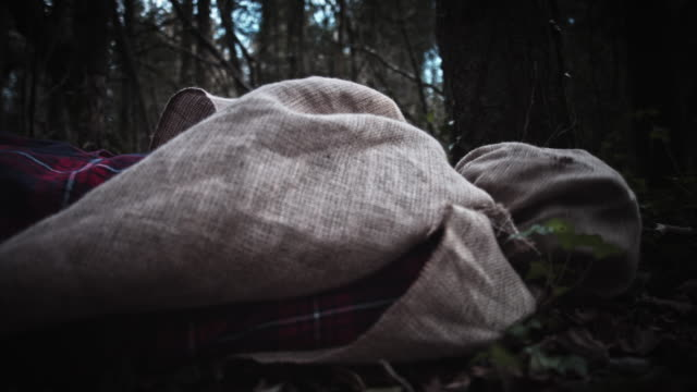 4K-Horror-Scarecrow-with-Sackcloth-Mask-Laying-in-Woods