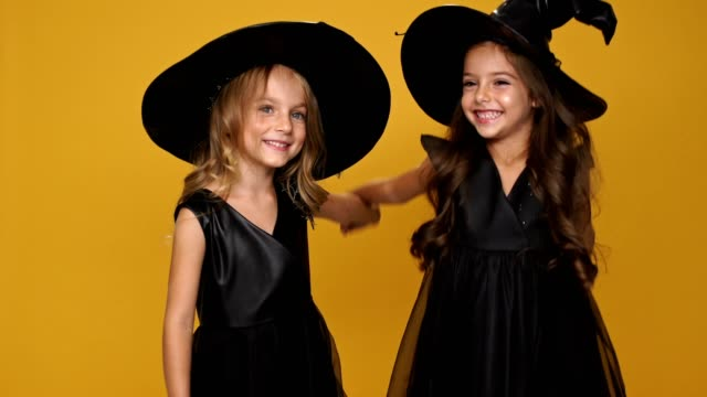 Little-pretty-friends-girl-in-black-witches-dresses-and-decorated-hats-holding-hands-each-other-and-smiling-over-orange-background