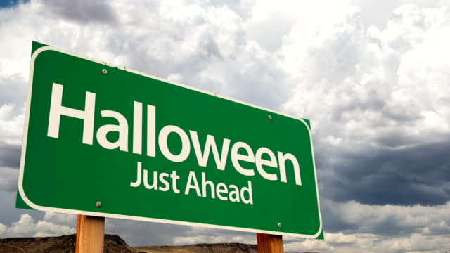 4K-Time-lapse-Halloween-Just-Ahead-Green-Road-Sign-and-Stormy-Cumulus-Clouds-and-Rain-