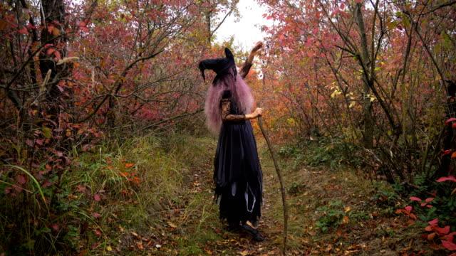 Joven-rosado-reactivos-de-búsqueda-bruja-de-pelo-en-el-místico-bosque-de-otoño-Preparación-de-Halloween-