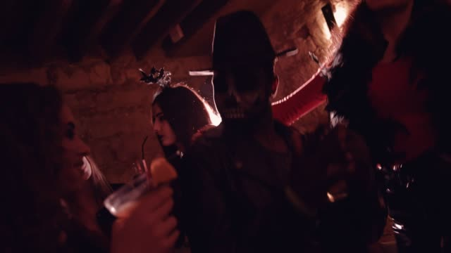 Multi-ethnic-friends-in-Halloween-customes-drinking-and-dancing-at-party