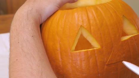 Man-Carves-a-Nose-in-a-Pumpkin-to-make-a-Jack-o-Lantern