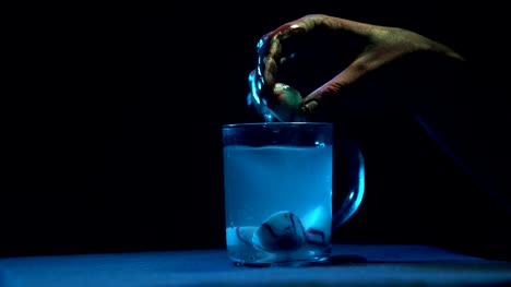 The-zombie-s-hand-takes-out-the-eyes-from-a-glass-beaker-with-liquid