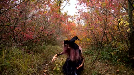Young-pink-hair-witch-in-hat-search-reagents-in-the-mystical-autumn-forest-Halloween-soon-