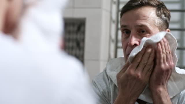 Hombre-mirando-en-el-espejo-y-limpiar-la-cara