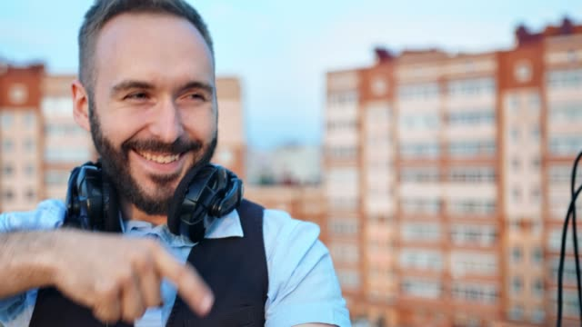 Close-up-face-of-cheerful-male-DJ-with-headphones-on-neck-having-fun-dancing-and-enjoying-party