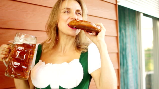 Young-sexy-Oktoberfest-girl---waitress-wearing-a-traditional-Bavarian-dress-serving-big-beer-mugs-and-eating-pretzel-on-wooden-background