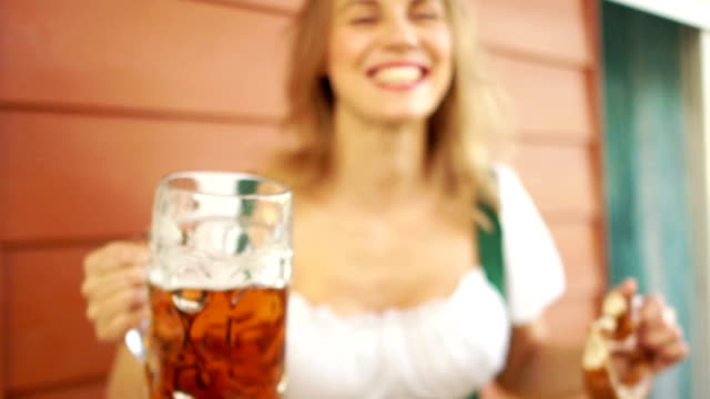 A-sexy-young-lady-drinks-beer-at-a-beer-festival-in-Germany-Close-up-large-beer-mugs-a-girl-laughing-cheerfully-red-lips-white-toothed-smile