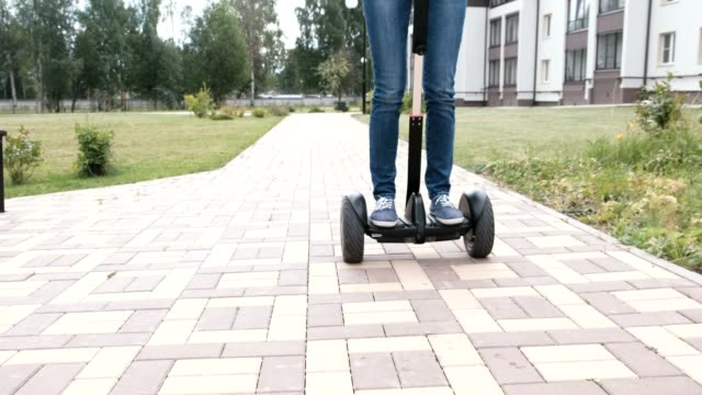 Brunette-woman-is-rolling-on-gyro-scooter-near-the-home-back-view-Close-up-legs-