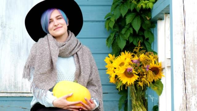 Una-hermosa-mujer-joven-está-sentada-en-el-porche-de-casa-de-campo-con-calabazas-