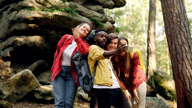 Grupo-multirracial-de-amigos-turistas-toman-selfie-en-bosque-con-rocas-en-el-fondo-con-smartphone-hombres-y-mujeres-posando-y-mostrando-gestos-con-las-manos-