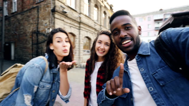 Point-of-view-shot-of-attractive-young-men-and-women-travelers-taking-selfie-in-the-street-posing-and-laughing-holding-camera.-Modern-technology-and-travelling-concept.