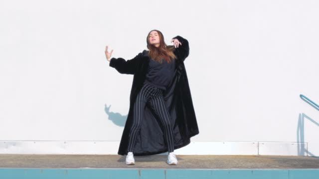 Young-Woman-Wearing-a-Large-Black-Winter-Coat-Dancing