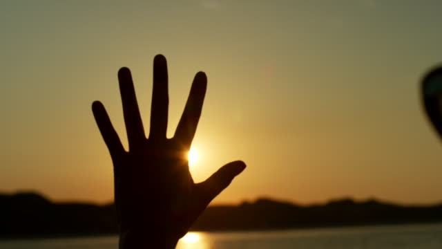 Silueta-de-mujer-hacer-Flare-forma-con-las-manos-contra-el-sol