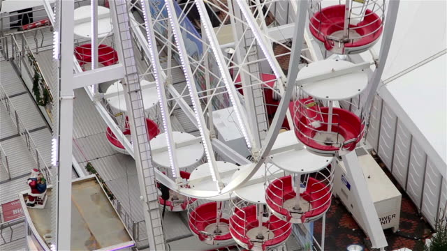 Close-Up-of-Ferris-Wheel-Cars-Spinning-Among-Christmas-Attractions-and-Lights
