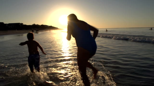 Mother-and-child-playing-on-beach-in-silhouette-at-sunset-Cape-Town
