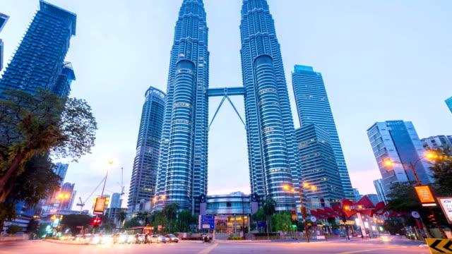 De-la-noche-al-día-HD-time-lapse-de-la-intersección-semáforo-en-frente-de-Suria-KLCC-con-torres-Petronas-