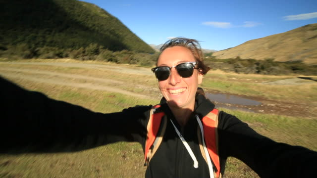 Young-female-hiking-takes-selfie-portrait-with-mountains-on-background