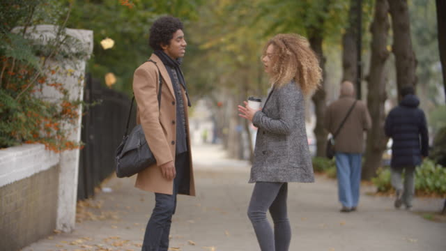 Stylish-Young-Couple-Talking-On-Fall-Street-In-City