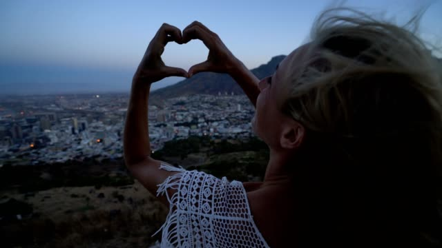 Young-woman-making-heart-shape-frame-in-Cape-Town-at-sunrise