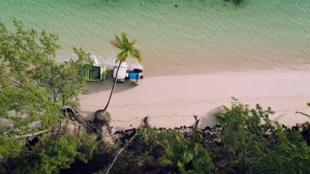 Aerial-video-of-Punta-Cana-beach-Beach-Sand-Cleaning-Truck-running-man-and-palm-trees-