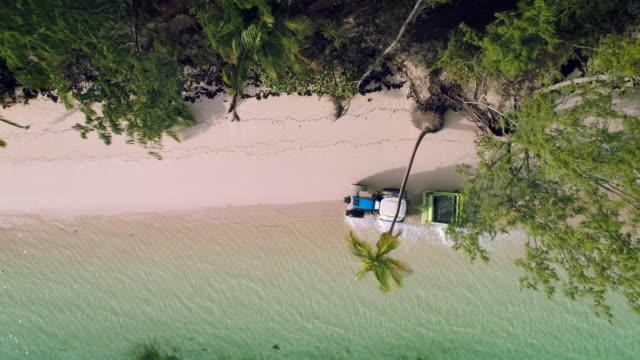 Tropical-island-beach-and-Beach-Sand-Cleaning-Truck-aerial-view