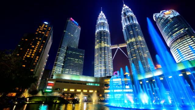 Parque-KLCC-Malasia---26-de-julio-de-2017:-Día-a-la-noche-doble-Torres-y-KLCC-Park-Sinfonía-fuente-lago-mostrar-cada-noche-lugar-histórico-viaje-de-Kuala-Lumpur-Malasia-4-K-Time-Lapse-(pan-doly-tiro)
