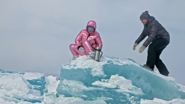Young-couple-has-fun-during-winter-walk-against-background-of-ice-of-frozen-lake-Lovers-are-sitting-on-large-blue-ice-floe-kissing-and-hugging-drinking-tea-from-thermos-bottle-Love-story-
