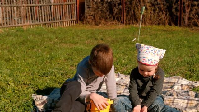 Hermano-y-hermana-ven-las-lombrices-en-el-césped-en-el-patio-trasero-de-la-casa-