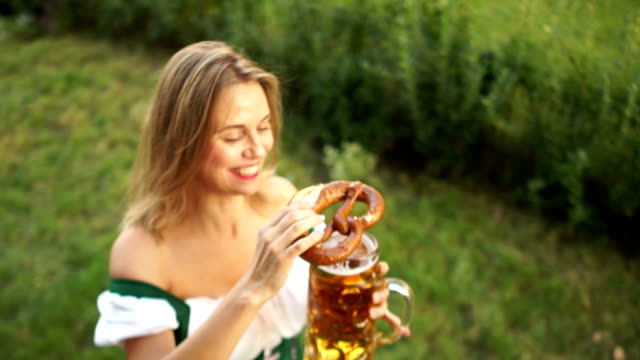 Young-sexy-girl-in-a-traditional-Bavarian-dress-buys-beer-and-pretzel-at-the-Oktoberfest-beer-festival-A-woman-laughs-cheerfully-and-enjoys-buying-On-a-green-background