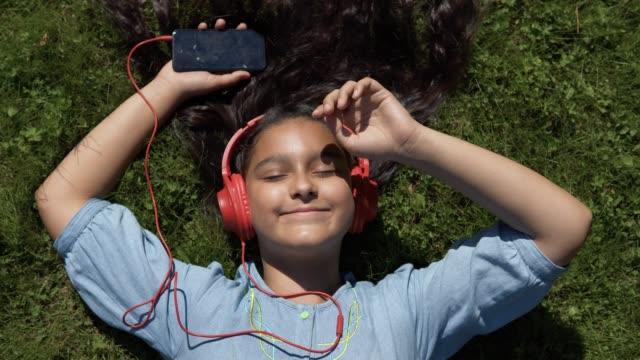 Junges-Mädchen-mit-langen-schwarzen-Haaren-anhören-von-Musik-über-Kopfhörer-bei-sonnigem-Wetter-auf-dem-Rücken-im-Park-liegt-4K