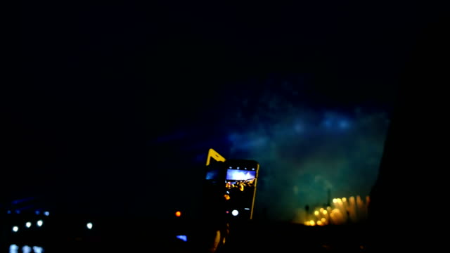 Fireworks-and-crowd-through-the-smartphone-screen-People-looking-at-the-fireworks-and-pyrotechnic-show-in-the-evening-bright-flashes-of-light
